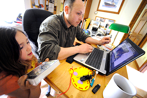Jesse McIntire and his daughter Orianna, 4,  hang out in the family study at their home in Orono, Maine Saturday, May 22, 2010. Jesse McIntire, a Maine Maritime Academy graduate (Class of 2003), is a chief mechanic on the Discoverer Spirit, a double-hulled drillship in the Gulf of Mexico. (Bangor Daily News/John Clarke Russ)