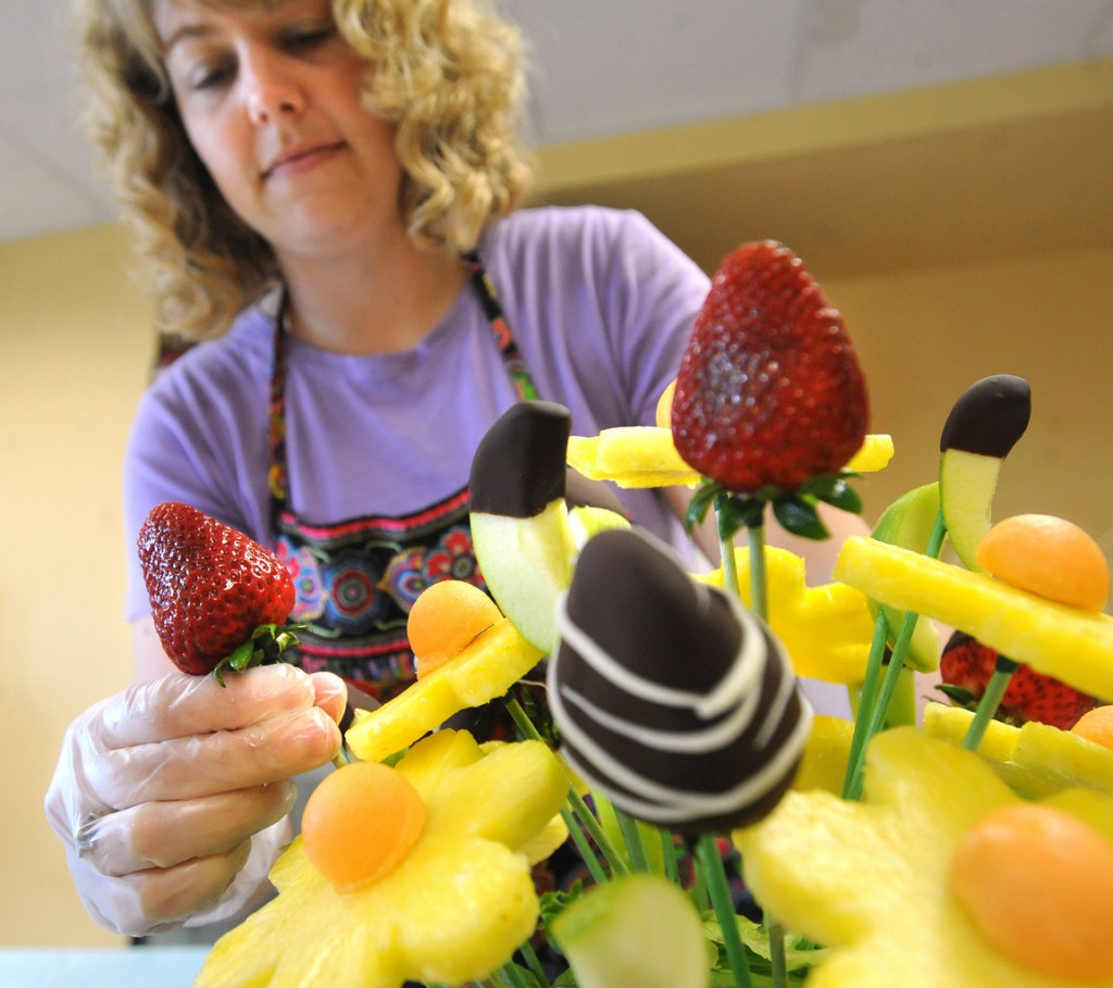 April Collins works on a custom fruit bouquet at her shop in Brewer on Tuesday, May 25, 2010. She makes fruit arrangements that are edible and healthy.   (Bangor Daily News/Gabor Degre)