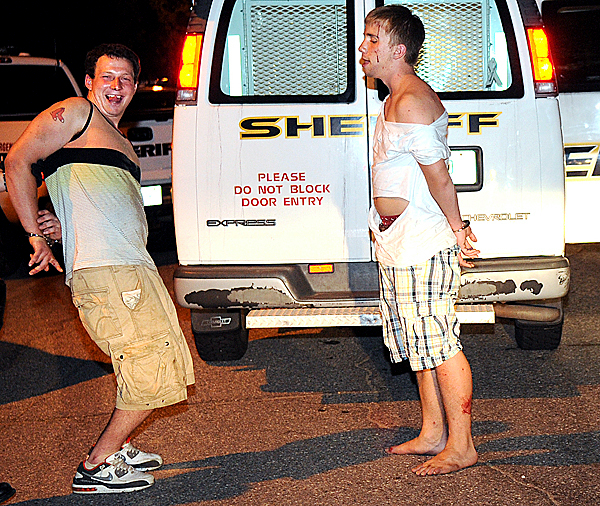 In this Tuesday, May 25, 2010 photo, a pair of Bates College students stand outside a sheriff's van and were among several arrested in a reported riot on the campus near the football field in Lewiston, Maine. Police in Maine's second-largest city say a number of Bates College students face charges after a gathering of 200 to 300 students outside a dormitory got out of control. (AP Photo/Sun-Journal, Russ Dillingham)