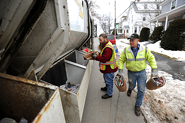 City of Bangor Public Works employees Rich LeGasse (left) Arthur Koch (right) sort recyclables curbside as they crisscross Bangor city streets Thursday. Bangor is considering a single-stream recycling program aimed at getting more households to participate in recycling. Single-stream recycling programs require no sorting by residents.  (BANGOR DAILY NEWS PHOTO BY KEVIN BENNETT)