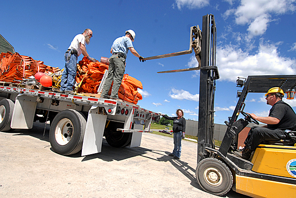 Nathan Thompson, center, a hazardous materials tech with the Maine Dept. of Environmental Protection's Bangor office, directs DEP maintenance mechanic Dave Flannery, right,  as he reverses his forklift  after unloading a pallet of oil containment booms onto a truck flatbed Thursday morning. Assisting were truck drivers George Davis and Lori Barrett (standing on ground) of L.E. Seidl Jr. Trucking LLC of East Baldwin, ME. The Maine D.E.P. has been readying 13,900 feet of oil containment booms to help with the Gulf of Mexico spill. BANGOR DAILY NEWS PHOTO BY JOHN CLARKE RUSS