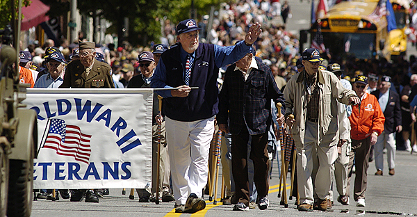 Lou Horvath ( holding banner and waving, in center) of Holden and other World War II veterans wave to the cheering crowds along Main Street during Monday morning's  Memorial Day Parade in downtown Bangor. BANGOR DAILY NEWS PHOTO BY JOHN CLARKE RUSS