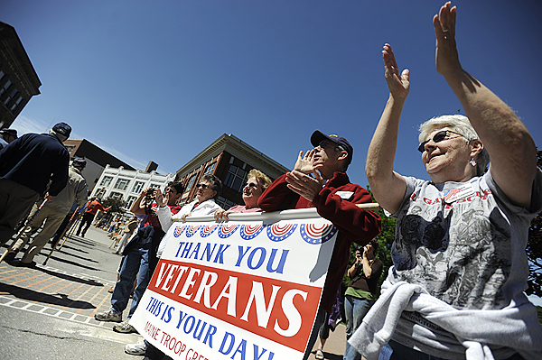 Cathy Czarnecki of Hermon, far right, Gaylen Jones, second from right,of Hampden and other members of the Maine Troop Greeters applaud military veterans and active duty personnel as they marched down Central St. enroute to Main Street during Monday's Memorial Day Parade in downtown Bangor. BANGOR DAILY NEWS PHOTO BY JOHN CLARKE RUSS