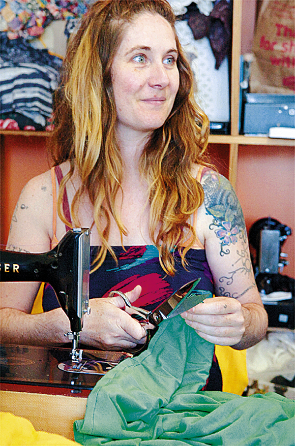 Jessi Sader works on a dress as she talks to a customer at her store and working space called Studio on Main Street in Orono on Thursday, May 27, 2010. BANGOR DAILY NEWS PHOTO BY BRIDGET BROWN