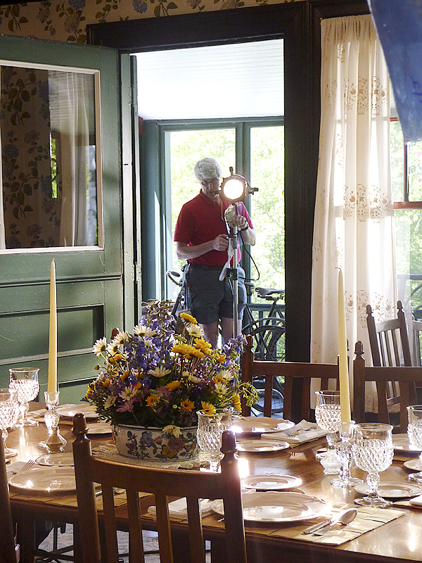 A member of the Florentine film crew sets up the lighting in the Roosevelt Cottage dining room as part of filming a documentary in the park last week.  BANGOR DAILY NEWS PHOTO BY SHARON KILEY MACK