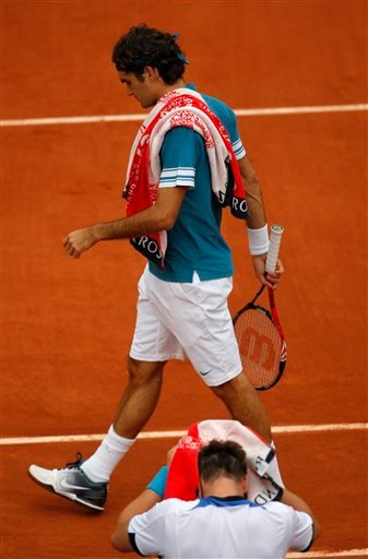 Defending champion Switzerland's Roger Federer walks past Sweden's Robin Soderling, sitting,  during their quarterfinal match of the French Open tennis tournament at the Roland Garros stadium in Paris, Tuesday, June 1, 2010. (AP Photo/Christophe Ena)