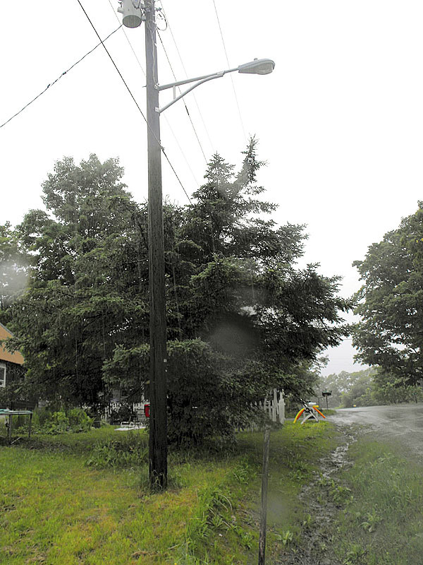 STACYVILLE -- A tree lies on some power lines on the Station Road in Stacyville on Thursday. Three Stacyvile residents, including two girls, were injured on Wednesday evening after a severe storm brought down a tree that pulled power lines on to the two girls. Both of the girls were burned in the accident. BANGOR DAILY NEWS PHOTO BY JEN LYNDS