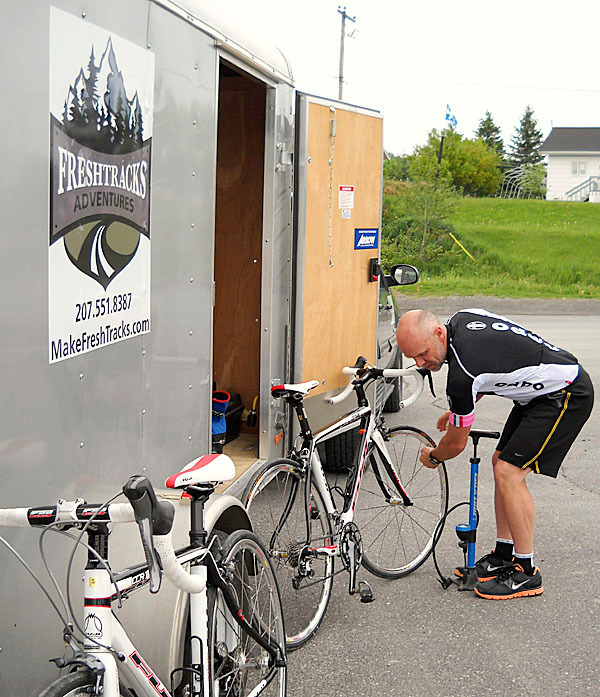 Cyclists get complete service on all Freshtracks Adventure rides, from pre-ride preparation to beverages and snacks on the road. Freshtracks co-owner and founder Mark Rossignol checks tire pressure on several bicycles before leading a group on a ride through the Temiscouta region of Quebec. JULIA BAYLY PHOTO