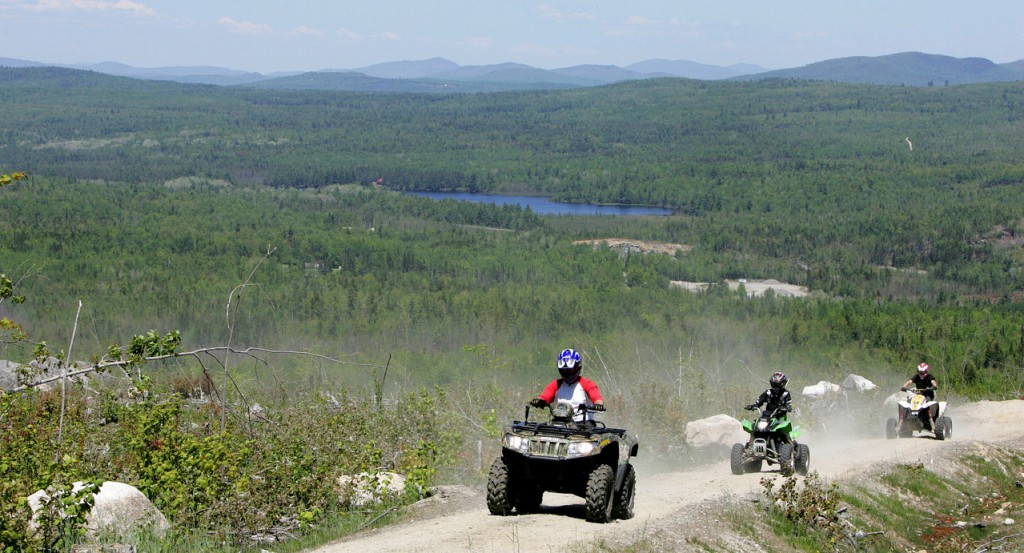 In this May 23, 2010 photo, Jude Stohl leads Leigha Cicchetto, and his son Ethan Stohl on a ride through Jericho Park's trail system, in Berlin, N.H. The park has one of the largest and longest trail systems in the Northeast designed for off-road vehicles. (AP Photo/Jim Cole)