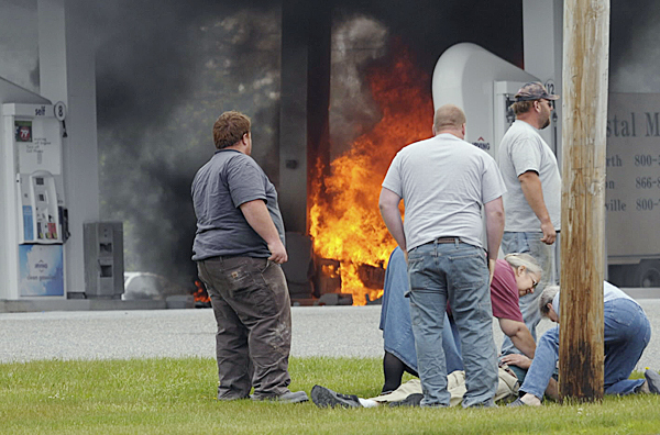 The driver of a medical delivery truck who was pulled from his burning truck is attended to by people at the scene after the truck struck a car and a gas pump at the Irving Circle K in Harrington Monday morning, June 7, 2010.  (Edwin Barkdoll photo)