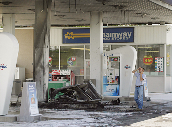An unidentified contractor examines the remains of a gas pump at the Circle K station in Harrington that was destroyed by fire  Monday after a medical delivery truck crashed  into the pump. Four local men rushed to the scene to rescue the driver from the vehicle which had burst into flames upon impact with the pump. BANGOR DAILY NEWS PHOTO BY RICH HEWITT