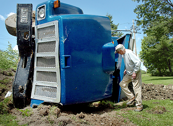 &quotI was glad I wasn't mowing my lawn,&quot said Robert Sherwood of Eddington as he examined a commercial truck transporting gravel which overturned in his yard Monday, June 7, 2010. Charles &quotHaley&quot Collins, Jr. said that he was traveling from Milford to Eddington on Route 9 when a passenger car crossed the center line, causing a collision. Penobscot County Sheriff's Office Deputy Sheriff Daren Mason said that the driver and passenger of the car sustained injuries but that they were not life-threatening. BANGOR DAILY NEWS PHOTO BY BRIDGET BROWN