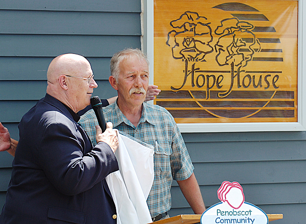 The Rev. Robert T. Carlson, (left) president of Penobscot Community Health Care, and Jack Barrows, housing program manager at the Hope House, unveil a sign at the Acadia Recovery Community in Bangor to symbolize the inclusion of the shelter as now a part of PCHC. The sign is original to the shelter which began in 1973 and is reinstating its original name. PCHC leadership is planning to offer more services for residents including primary care, expanded shelter, a day program and access to dental care. BANGOR DAILY NEWS PHOTO BY BRIDGET BROWN