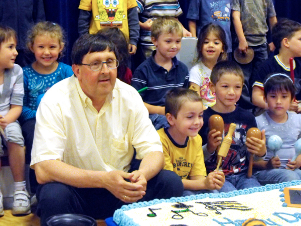 VAN BUREN -- Surrounded by his kindergarten students, John Parent, who has taught that grade for 38 years in SAD 24 in Van Buren, listens to a speaker during a surprise retirement assembly held in his honor in Van Buren District Secondary School Monday afternoon. Parent was honored during the gathering for his lengthy teaching career, his dedication to the profession and for making what many speakers said was a lifelong impact on students and student athletes in the district. BANGOR DAILY NEWS PHOTO BY JEN LYNDS