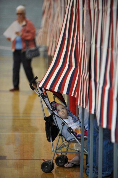 PRIMARY COLORS: 14-month-old Olivia Perry of Brewer seems fascinated by the colorful polling booth curtain as her mother Farrah Perry makes her selections in a polling booth at Brewer Auditorium Tuesday morning, June 8, 2010. &quot All the  issues are important but the governor's race is key, &quot said Perry. Walking out of a polling booth behind them was Charlotte Kacer of Brewer. (Bangor Daily News/John Clarke Russ)