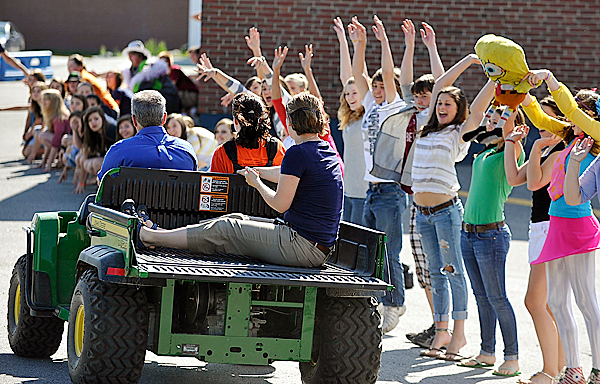 With history teacher Herb Taggart driving and English teacher Rebecca Petersen in the back bed of the vehicle, English teacher Andrea Martin (in front passenger seat) filmed a throng of lively students outside the classrooms during the high school's lip sync music video production Wednesday morning. BANGOR DAILY NEWS PHOTO BY JOHN CLARKE RUSS