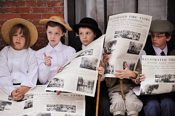 Left to right: Fairmount School fourth graders Alana Broughton (cq),10, Rya Morrill (cq), 10, Brendan Martin (cq), 10, Alexander Ogden (behind newspaper), 10, and David Rubin, 10, listened to other classmates as they took turns reading the headlines from a 1911 edition of the Bangor Daily Commercial during the fourth graders' history presentation at the Bangor Museum and History Center Thursday morning, June 10, 2010. Jean Schmick , a fourth grade teacher at Fairmount School,  helped organize the student's presentation which served as a service learning project and part of their Maine history curriculum. Their museum visit was the culmination of their research, writing and public speaking practice, said Schmick. BANGOR DAILY NEWS PHOTO BY JOHN CLARKE RUSS