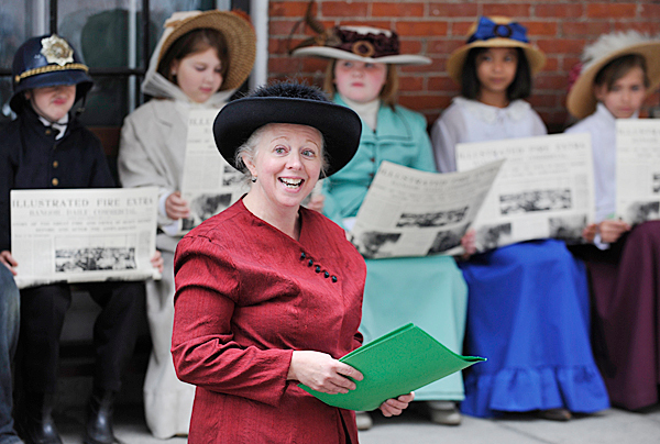 Left to right: Fairmount School fourth grade teacher Jean Schmick delivers opening they took turns reading the headlines from a 1911 edition of the Bangor Daily Commercial during the fourth graders' history presentation at the Bangor Museum and History Center Thursday morning, June 10, 2010. Schmick helped organize the students' presentation which served as a service learning project and part of their Maine history curriculum. Their museum visit was the culmination their research, writing and public speaking practice, said Schmick. BANGOR DAILY NEWS PHOTO BY JOHN CLARKE RUSS