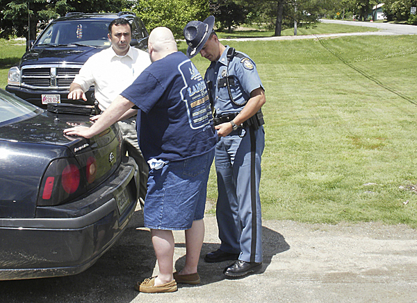 Walter Ramsdell III, 39, (center) is arrested on child pornography charges by State Police Trooper Kyle Ouellette outside Care-A-Lot Day Care in Eddington on Wednesday, June 9, 2010.  At left is Detective Special Agent Mike McFadden of the State Police Computer Crimes Unit, which had been monitoring activity on a network where child pornography is shared, according to the state police. (Photo courtesy of Maine Dept. of Public Safety)