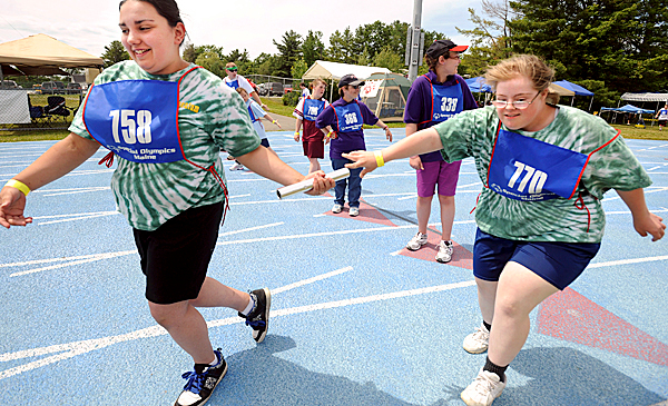 Team Momentum's Julie Dean (right) hand the batton to Jessica Ashley in the 4x100 meter relay.  They are among the people participating in the 2010 Special Olympics Maine SUmmer Games in Orono this weekend. BANGOR DAILY NEWS PHOTO BY GABOR DEGRE