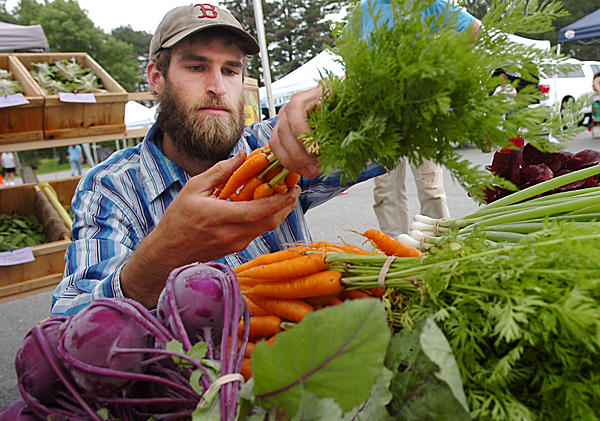 Gene Ripley of Ripley Farm in Troy replenishes his stand with fresh carrots at the Orono Farmers' Market on Tuesday. Located off College Avenue, the market operates from 2 to 5:30 p.m. Tuesdays and 8 a.m.-1 p.m. Saturdays during the summer and early fall.  BANGOR DAILY NEWS FILE PHOTO BY KATE COLLINS