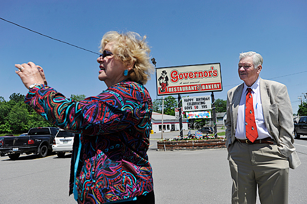 GOVERNING FAMILY : The Leith Wadleigh, right, watches his wife of 53 years and business partner, Donna Wadleigh as she took some snapshots of the outside of their Governor's Restaurant in Old Town location Tuesday, June 15, 2010. The Wadleigh family is celebrating the restaurant chain's 50th anniversary.  BANGOR DAILY NEWS PHOTO BY JOHN CLARKE RUSS