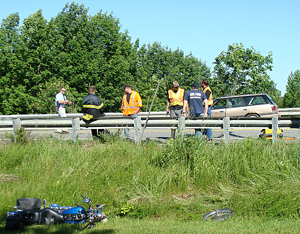 A motorcyclist and a passenger on the bike (foreground) were were critically injured Tuesday afternoon when they reportedly were passing a vehicle (in background) that was turning into a driveway off Route 150 in Parkman. The man and woman, whose names have not yet been released by police, were airlifted by Lifeflight helicoper to Eastern Maine Medical Center in Bangor. State police are currently at the scene. No other details are yet available. BANGOR DAILY NEWS PHOTO BY DIANA BOWLEY