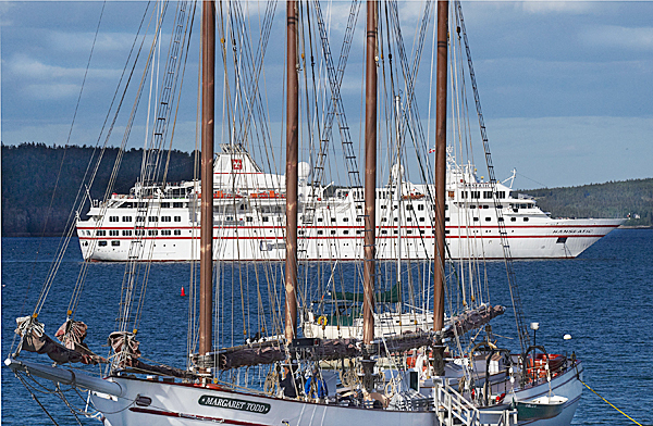 In this  May 27, 2010 photo, the four-masted schooner Margaret Todd sits at berth while the cruise ship Hanseatic sits at anchor in Bar Harbor, Maine. (AP Photo/Michael C. York)