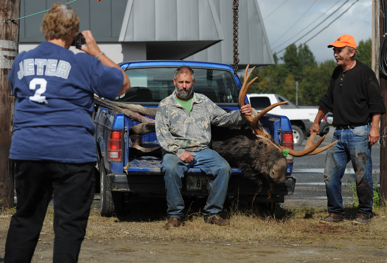 Martha Dickinson of Oakfield (left) photographs her husband, Robert Dickinson, and Carl Croy of Oakfield at the tagging station at M.A.C.S. Trading Post in Houlton on Monday. Robert Dickinson's moose, tagged on the first day of the split-session moose hunt weighed 752 pounds.  (BANGOR DAILY NEWS PHOTO BY KEVIN BENNETT)  CAPTION  Martha Dickinson, left, of Oakfield, photographs her husband, Robert Dickinson, center, and Carl Croy, right, at the tagging station at M.A.C.S. Trading Post in Houlton after Robert dropped a 752 pound bull moose on Monday, September 28, 2009. (Bangor Daily News/Kevin Bennett)