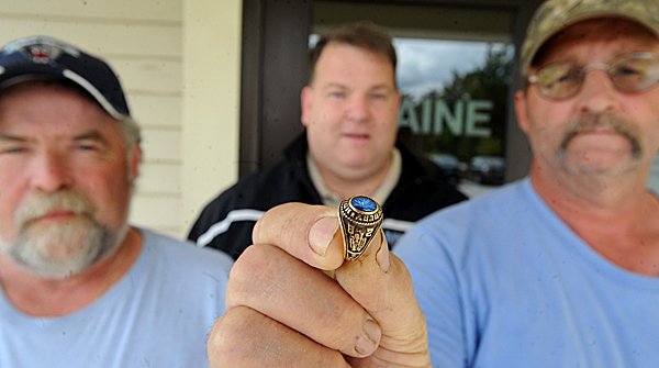 Steve Stone (left), Roderick Thompson (right) and Andy Brown pose with a ring that Stone and Thompson found recently while working on a parking lot at the University of Maine in Orono.  The ring turned out to be a 1982 high school class ring that was lost by former University of Maine student Lisa Prue during a snowball fight 27 years ago.  Brown, who is a UM dispatcher, tracked down Prue, who currently lives in Worcester, Mass. BANGOR DAILY NEWS PHOTO BY GABOR DEGRE
