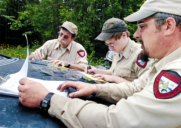 Wildlife biologist Craig McLaughlin (from left), Unity College senior Everett Smith and biologist Randy Cross compare notes after a morning of checking bear traps for the Department of Inland Fisheries & Wildlife's annual spring black bear survey Monday, June 14, 2010. (Bangor Daily News/Bridget Brown)