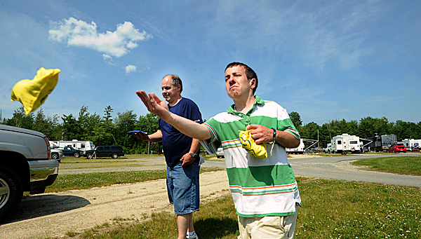 Justin Jimmo of Bangor (right) tosses a bean bag while plaing a game wigh his father Jody Jimmo while they were staying at the Yimberland Acres RV park in Trenton.  They have camped in Northern Maine a lot but stayed at the RV park before.  &quotI love it here.  I want to start coming back in this direction&quot Jody Jimmo said.  BANGOR DAILY NEWS PHOTO BY GABOR DEGRE