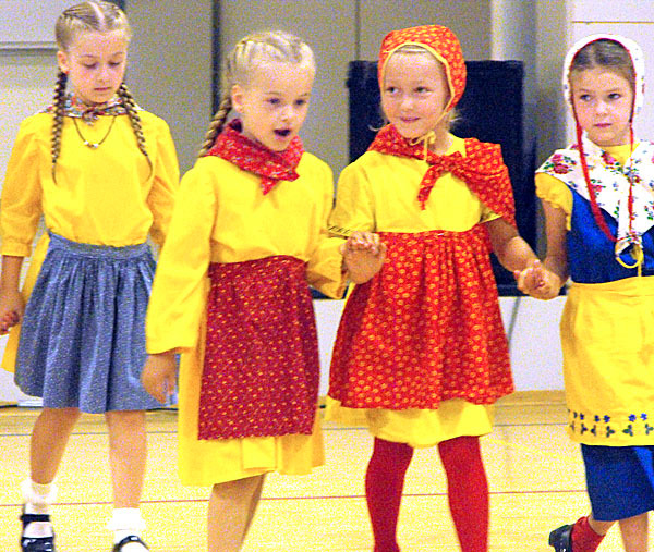 Four young girls who are part of the New Sweden Little Folk Dancers join hands to dance during a ceremony that was part of the 140th Midsommar Festival. The traditional dance group is comprised of children from the area. Dressed in traditional costumes made of resplendent yellow, blue and white, the children danced to traditional music.  BANGOR DAILY NEWS PHOTO BY JEN LYNDS