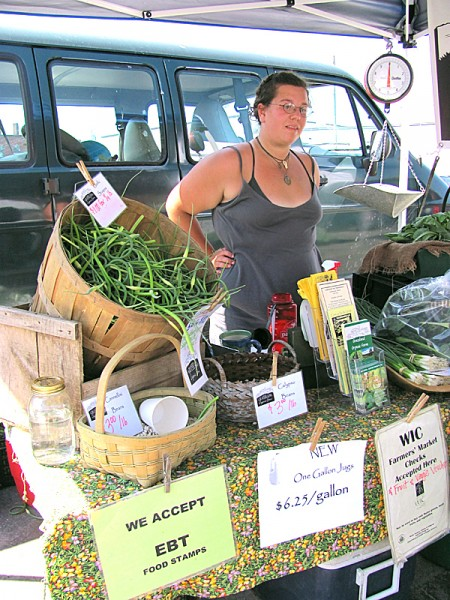 Margosia Jadkowski, an employee of Grassland Organic Farm in Skowhegan, operates a booth at the Skowhegan Farmer's Market on Saturday, which was the first day of a new &quotDouble Dollars&quot program for people who receive government food subsidies. Buy Photo