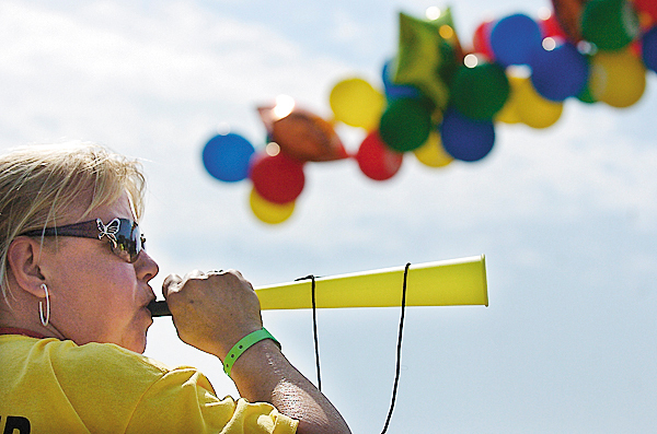 Volunteer Terry Sidelinger of Richmond blows on her noisemaker as she and and may others cheer cyclists as they approach the Belfast finish of the 26th Annual Trek Across Maine for the American Lung Association.  The three-day , 180-mile bike ride started Friday from Sunday River and ended Sunday in Belfast.   BANGOR DAILY NEWS PHOTO BY JOHN CLARKE RUSS