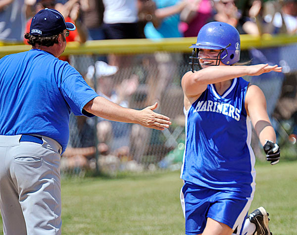 Deer Isle-Stonington player Britnie Jones, (21), gets a high-5 from coach Terry Siebert as she passes third base after hitting a two run homerun in the first inning of their game versus Ricmond at Brewer, Saturday, June 19, 2010. BANGOR DAILY NEWS PHOTO BY MICHAEL C. YORK