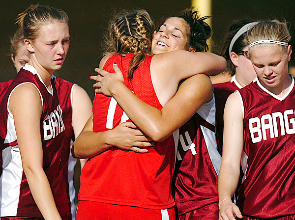 Following Bangor's 1-0 loss to South Portland for the Class A softball championship game, senior pitcher Samantha Bedore (center) gets a hug from South Portland's Kalie Swiger at Saint Joseph's College in Standish on Saturday, June 19, 2010. BANGOR DAILY NEWS PHOTO BY BRIDGET BROWN