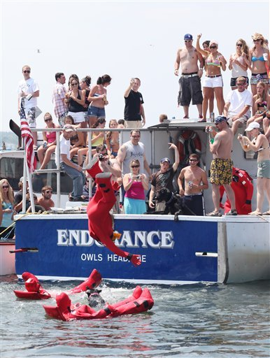A lobster boat race spectator jumps off a boat during a race to put on a survival suit Sunday, June 20, 2010 in Rockland, Maine.  In all, more than 110 boats raced over the weekend as Maine's annual lobster boat racing season kicked off. (AP Photo/Joel Page)