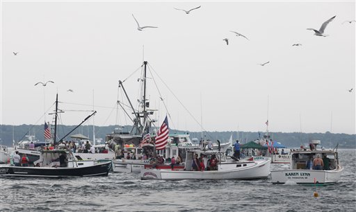 Spectators and participants gather along the race course Sunday, June 20, 2010 during a lobster boat race in Rockland, Maine.  In all, more than 110 boats raced over the weekend as Maine's annual lobster boat racing season kicked off. (AP Photo/Joel Page)