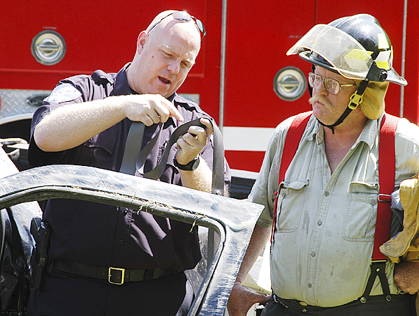 Lincoln Police Chief Scott Minckler examines a seat belt for signs of melting common when they are worn in high-speed impacts as a Lincoln firefighter looks on. (Bangor Daily News/Nick Sambides Jr.)