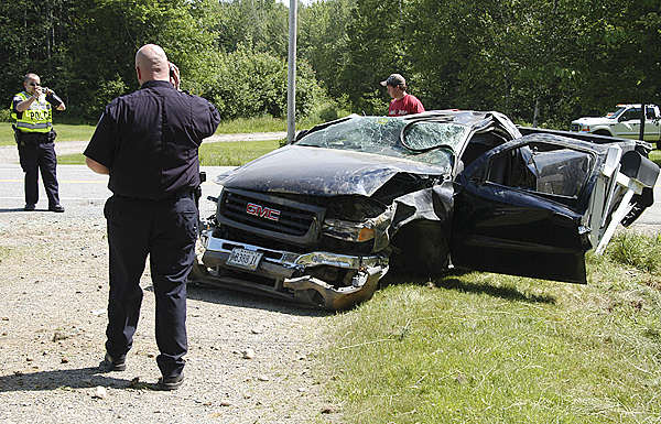 Lincoln Police Officer Robert Smith [left] photographs a wrecked GMC Sierra pickup truck as Police Chief Scott Minckler speaks on a cellphone and wrecker operator Evan Thornton scouts for large pieces of wreckage at an accident scene on Route 6 in Lincoln on Tuesday.(Bangor Daily News/Nick Sambides Jr.)
