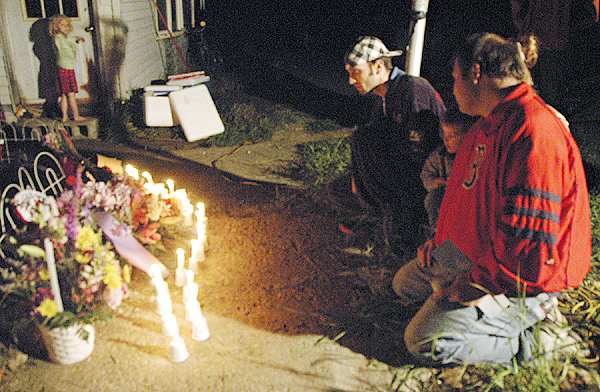 Raymond Grindle, 45, of Howland, kneels with other family and friends on Monday at the memorial for his daughter, Kourtney Grindle Murray, 24, and Christina Pegg, 18, in front of the home on Military Road in Greenbush where both lived prior to being killed in an Enfield car accident last week. (Bangor Daily News photo by Nick Sambides Jr.)