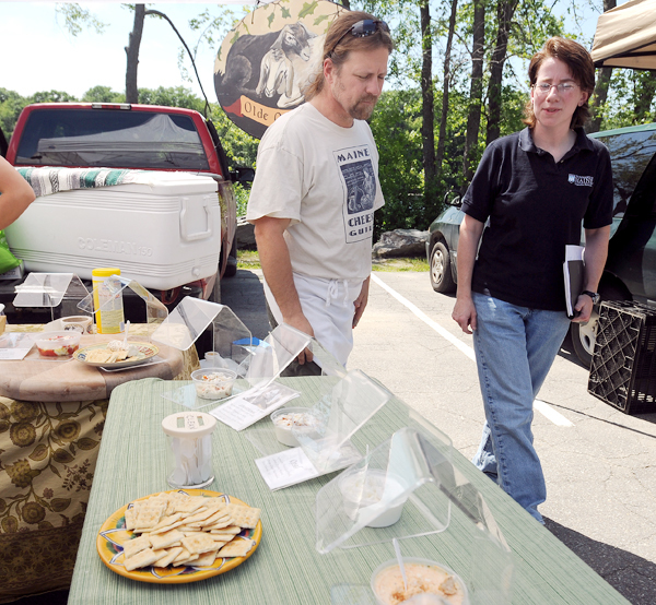 Beth Calder (right), a food science specialist with the University of Maine Cooperative Extension, talks to Scott Belanger, the co-owner of the Olde Oaks Farm, during the Orono Farmers' Market Tuesday, June 23, 2010.  Calder was at the farmers' market to talk to vendors and customers about food safety and food handling tips.  Belanger, who sells goat and cow cheese, said that he agrees with the safety guidelines and has made several changes in his booths at farmers markets.  BANGOR DAILY NEWS PHOTO BY GABOR DEGRE