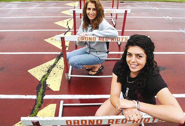 Orono High School junior Alex Crocker (right) followed in her mother Chris Crocker's footsteps when she won the 300-meter hurdles at the Class C track and field championships earlier this month at Foxcroft Academy. Crocker and her mother are seen here at the Orono High School track Wednesday, June 23, 2010. (Bangor Daily News/Bridget Brown)