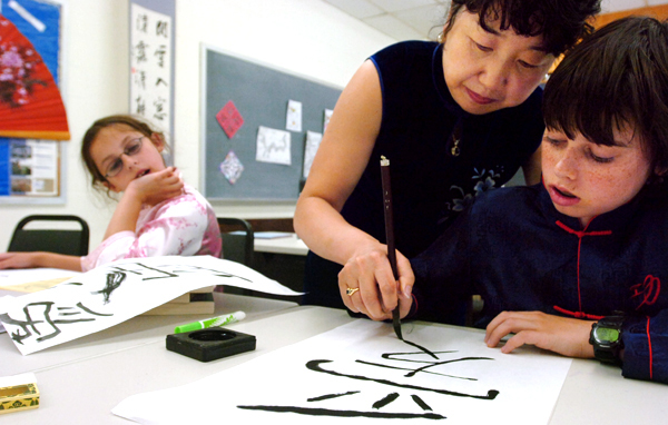 Jing Zhang (center), president of the Bangor Chinese School,  helps Tommy McCarthy draw the Chinese character for love as his sister Abby looks on. BANGOR DAILY NEWS PHOTO BY GABOR DEGRE