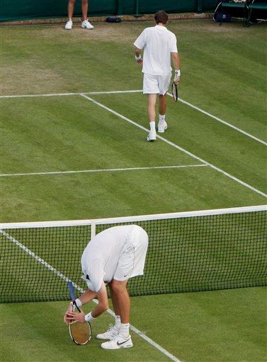 John Isner of the US, left, bends over and holds his head during his epic singles match against Nicolas Mahut of France at the All England Lawn Tennis Championships at Wimbledon, Wednesday, June 23, 2010. Play was suspended for bad light with scores tied at 59 all in the 5th set. (AP Photo/Mark Baker)