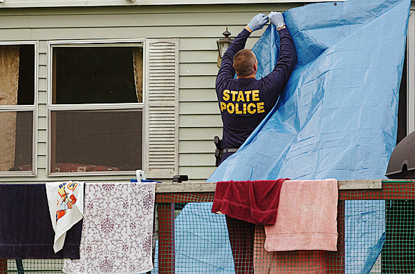 Detective Jay Pelletier secures a tarp over the entrance of a home which was the scene of a triple homicide on U.S. Route 1 in Amity on Thursday morning, June 24, 2010. Detectives say two men and a young boy were stabbed to death. Jeffrey Ryan, 55, his son Jesse Ryan, 10, and Jason Dehahn, 30, who was visiting the Ryan residence, were found dead Wednesday night by a relative. BANGOR DAILY NEWS PHOTO BY BRIDGET BROWN