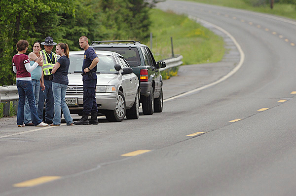 Maine State Police talk with an unidentified woman (left), Tamara Strout (second from left), and Mariah Ryan, 16, (second from right) at the scene of a triple homicide on U.S. Route 1 in Amity on Thursday, June 24, 2010. Ryan's father Jeffrey Ryan, 55, her brother Jesse Ryan, 10, were two of the victims. The third was Jason Dehahn, 30, who was visiting the Ryan residence. BANGOR DAILY NEWS PHOTO BY BRIDGET BROWN