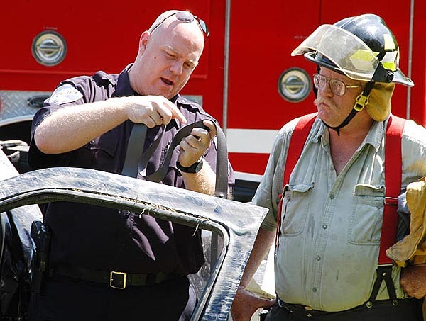 Lincoln Police Chief Scott Minckler examines a seat belt for signs of melting common when they are worn in high-speed impacts as a Lincoln firefighter looks on. BANGOR DAILY NEWS PHOTO BY NICK SAMBIDES JR.