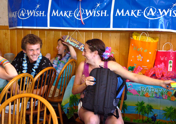 Hampden resident Ericka Garcia, 16, (right) opens gifts alongside friends including Stephen Hoffman, 15, (left) and Sarabeth Miller, 16, (second from left) during a luau party in Garcia's honor put on by the Make-A-Wish Foundation at Dysart's in Hermon on Tuesday, June 22, 2010. The foundation is also granting Garcia's wish--to travel to Hawaii.   (Bangor Daily News/Bridget Brown)